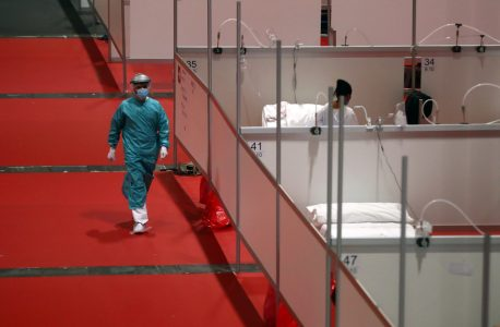 A member of medical personnel walks through the hall of a temporary hospital inside IFEMA conference centre, amid the coronavirus disease (COVID-19) outbreak, in Madrid, Spain, April 2, 2020. REUTERS/Sergio Perez