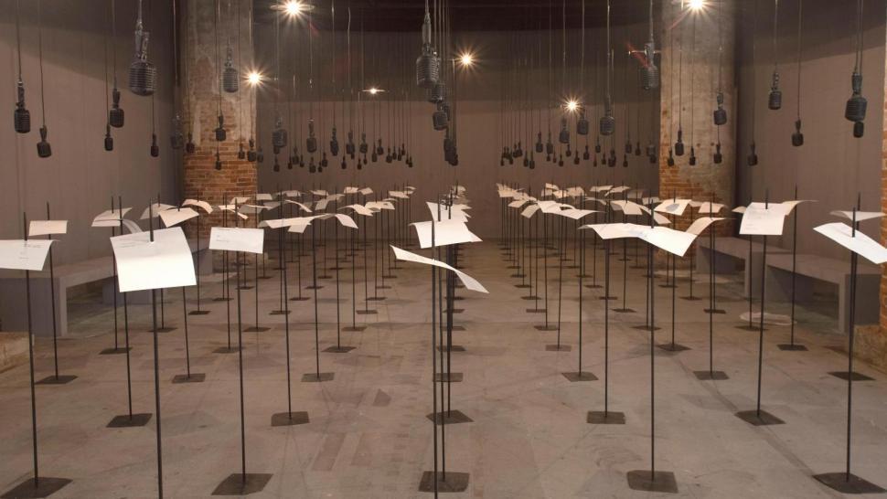 Shilpa Gupta (b. 1976), For, In Your Tongue I Cannot Fit, 2017-2018, instalación de sonido con 100 micrófonos, texto impreso y varas de metal. Foto: Italo Rondinella