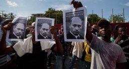 """Milhares de haitianos seguravam cartazes de protestos e pediam a Vladimir Putin, presidente russo: """"Por favor, nos ajude"""". Crédito: Dieu Sputnik News."""