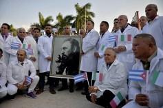 Médicos e enfermeiras da Brigada Médica Internacional Henry Reeve, de Cuba, posam com um retrato do falecido líder cubano Fidel Castro enquanto se despedem antes de viajar para a Itália, que foi duramente atingida, para ajudar na luta contra a pandemia de coronavírus COVID-19, na Unidade Central de Cooperação médica em Havana, em 21 de março de 2020. - A Itália fechou todas as fábricas não essenciais depois de registrar outro número recorde de coronavírus que levou suas mortes a 4.825 - mais de um terço do total do mundo e um lembrete sombrio de que a pandemia permanece fora de controle. Crédito: Yamil Lage / AFP.