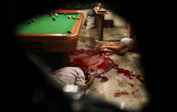 Cadáveres en un salón de billar después de un ataque de asaltantes enmascarados cerca de San Pedro Sula, Honduras. Foto © Esteban Félix.