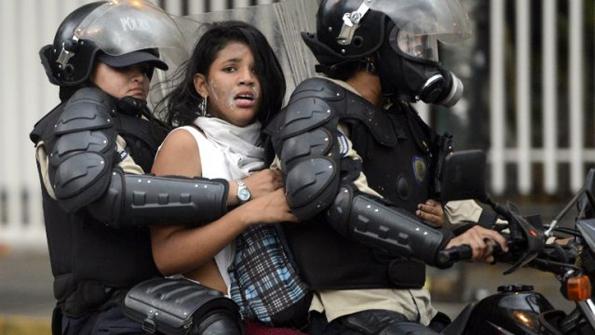 Una activista contra el gobierno de Maduro es arrestada por la policía nacional durante una protesta en Caracas. AFP / END.