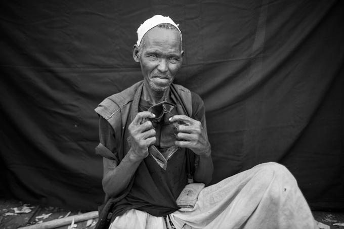 Hassan, que no está seguro de su edad, pero que cree que tiene entre 60 y 70 años, posa para un retrato en el campo de refugiados de Jamam, en el condado de Maban, Sudán del Sur. El conflicto bélico obligó a Hassan y a su familia a huir de su hogar en la aldea de Maganza, en el estado de Nilo Azul de Sudán. Lo más importante que pudo llevarse consigo es la cartera vacía que sujeta. A pesar de que ahora es un indigente, abandonó Maganza con dinero suficiente para comprar comida para su familia durante el viaje de veinticinco días que realizaron hasta la frontera de Sudán del Sur. Foto © Brian Sokol.