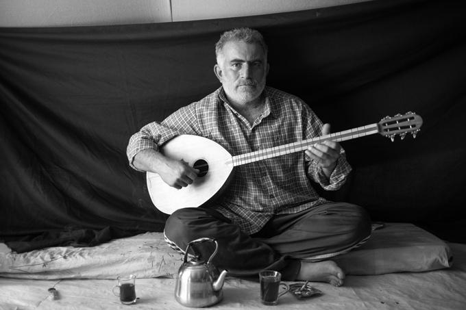 Omar, 37 años, en su tienda de campaña en el campamento de refugiados de Domiz en Kurdistán, Iraq (16 de noviembre de 2012). Omar huyó de Damasco con su esposa y sus dos hijos la noche en que sus vecinos fueron asesinados. «Entraron en la casa y descuartizaron a mi vecino y a sus dos hijos. Arrastraron los cuerpos hasta la calle, donde los encontramos por la mañana.» Lo más importante que Omar se llevó es su buzuq, el instrumento que muestra en esta fotografía. «Tocar me llena de un sentimiento de nostalgia y me recuerda a mi tierra natal. Por un momento, alivia un poco mis penas.» Foto © Brian Sokol.