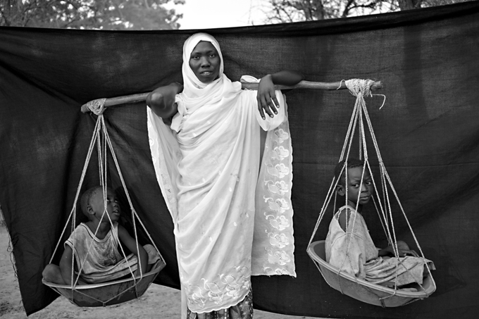 Varios meses antes de que se tomara esta fotografía, los constantes bombardeos obligaron a Dowla, de 22 años, y a sus seis hijos a huir de su pueblo, en el estado de Nilo Azul de Sudán. Lo más importante que pudo llevarse consigo es el palo de madera que balancea por encima de los hombros, con el que transportó a sus seis hijos durante el viaje de diez días que realizaron desde Gabanit hasta Sudán del Sur. En ocasiones, los niños estaban demasiado cansados para andar, lo que la obligaba a cargar a dos de ellos en cada lado. Campamento de refugiados de Maban, Sudán del Sur. Foto © Brian Sokol.