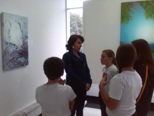 La pintora María Claudia López explicando al alumnado parte de su obra expuesta.