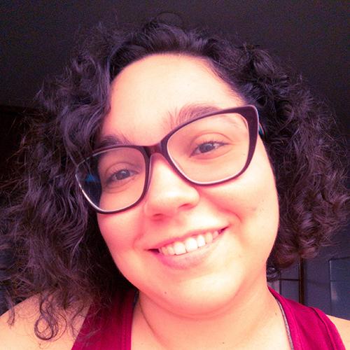 Foto de Mayara Barros. Uma mulher branca, de olhos castanhos, óculos, cabelos cacheados na altura do ombro, usando camiseta vermelha.