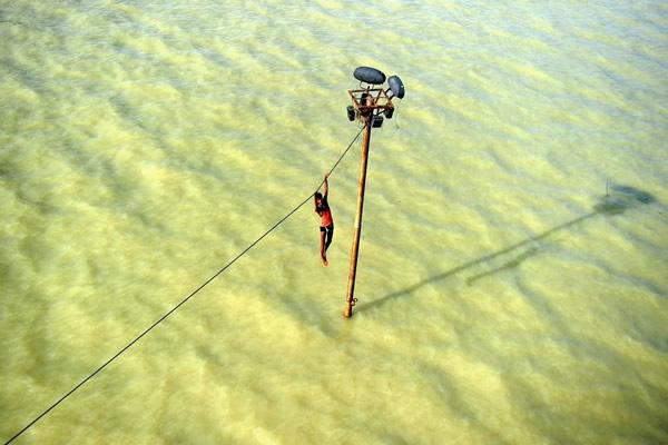 Las Imágenes más Sobrecogedoras de 2013 - Un joven hindú sobreviviendo a las inundaciones en India.