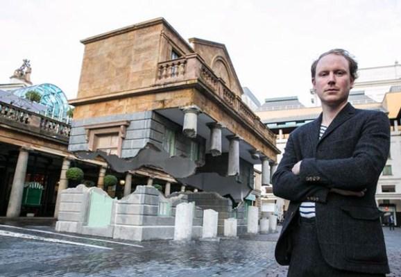 Alex Chinneck posando con su ilusión arquitectónica