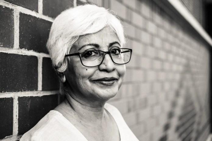 woman wearing eyeglasses leaning on brick wall