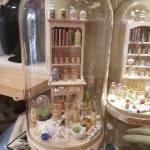 Cloche de verre dans laquelle une sculpture représente un établi de créativité