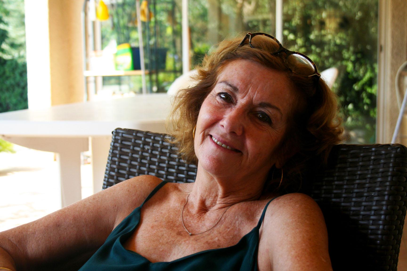 Geniève Grenier, assise dans le salon de jardin près de la piscine
