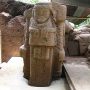 The small human figure—is it the representation of the ancestor?—carried at the back of the personage of Monument 215.