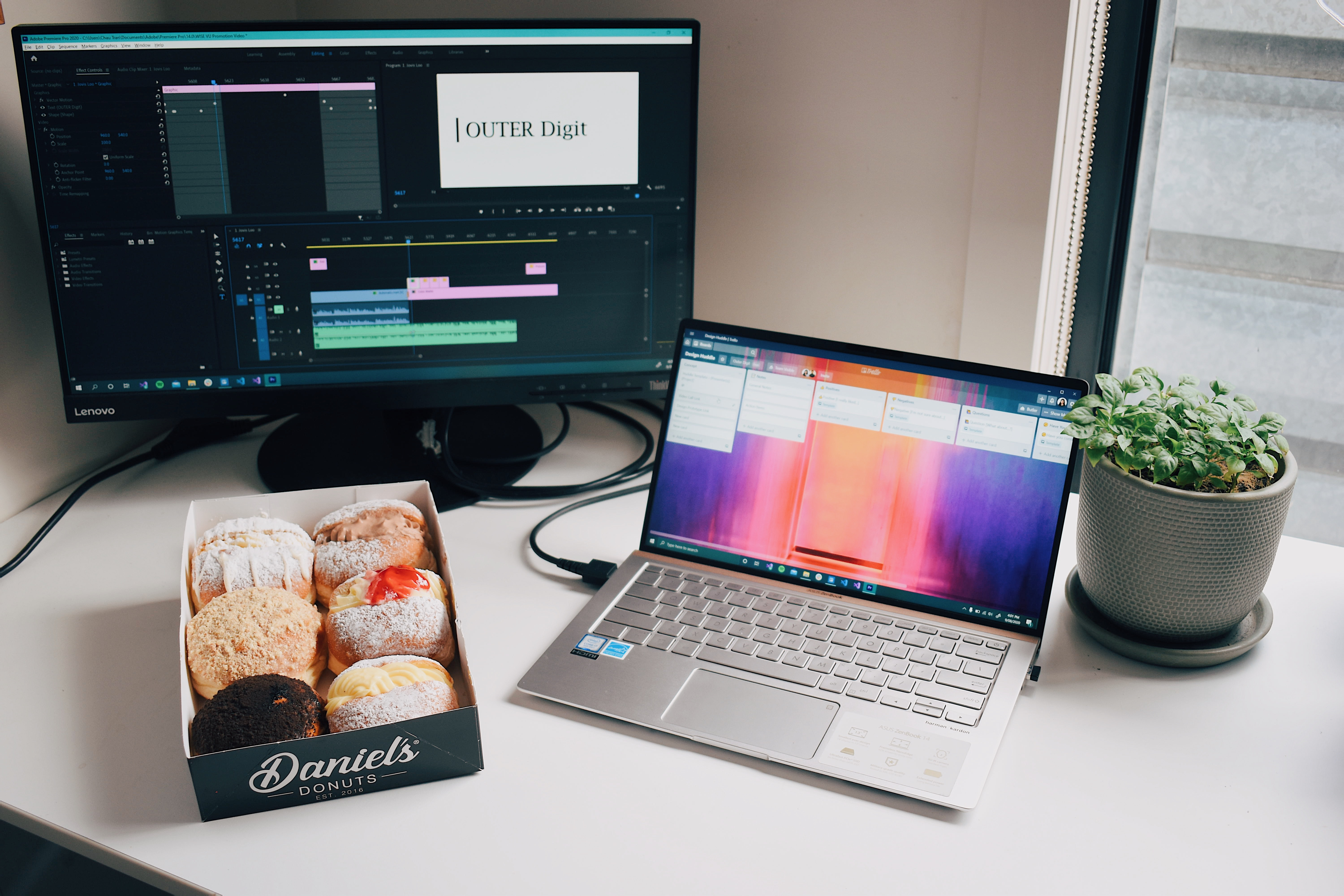 An office workspace with a laptop, a monitor, a plant, and a box of donuts.