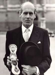 Leonard Cheshire holding his Order of Merit in front of Buckingham Palace