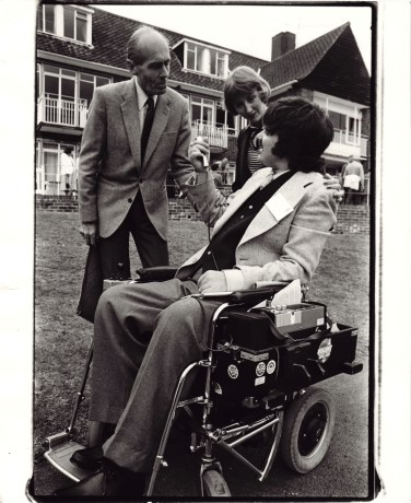 A man in a wheelchair interviewing a man and woman outside a large house