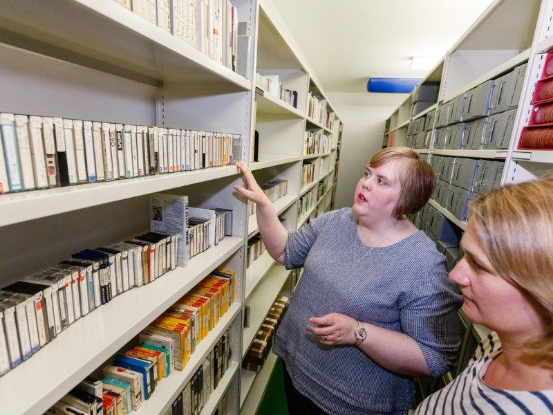 Two women stood in a film archive