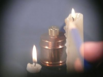 This image shows the view through a Camera Lucida. The candles and the metal cannister are projected and you can see the hand drawing the objects.