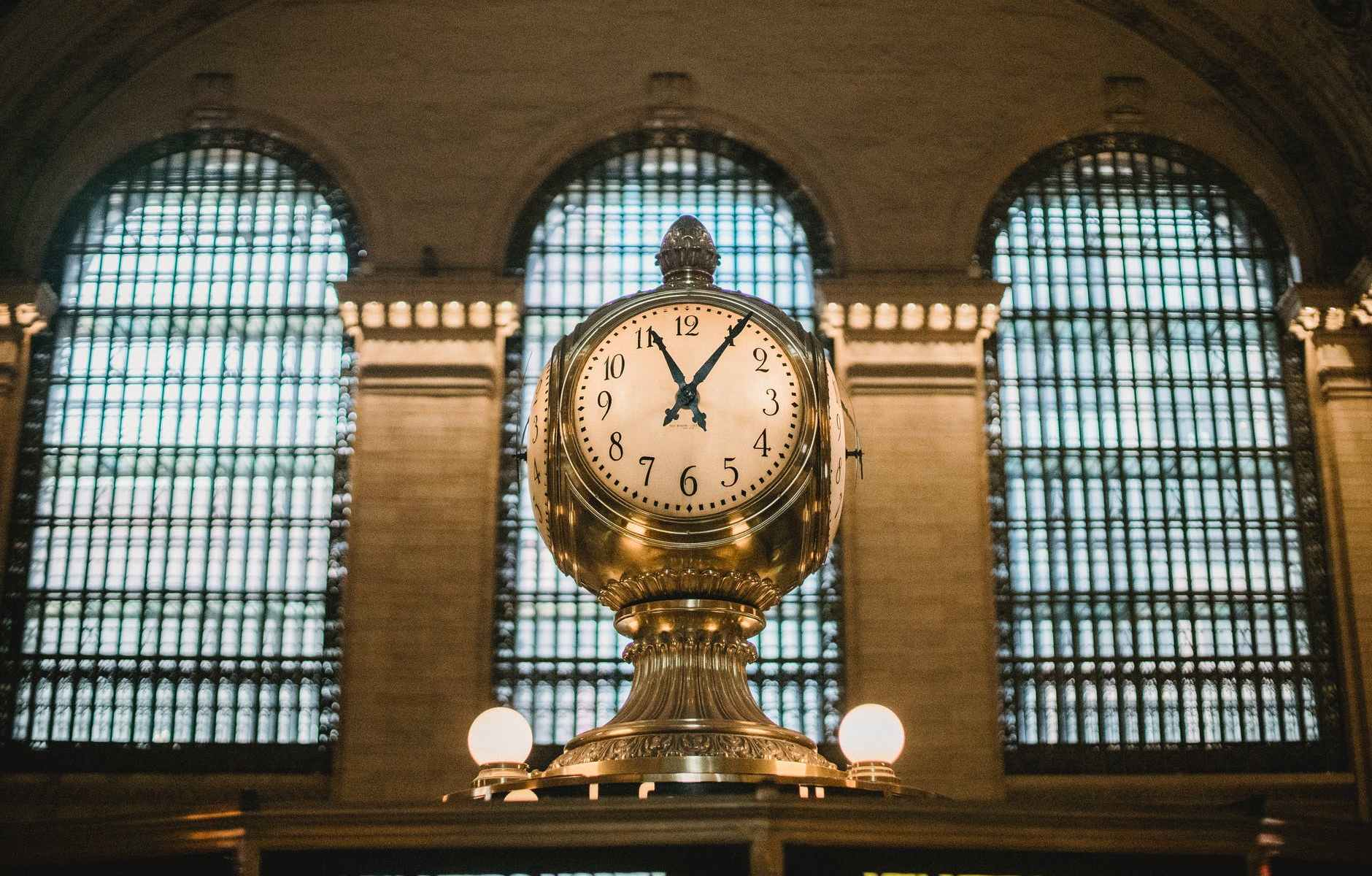 vintage golden clock in aged railway station terminal with arched windows