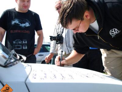 Kapsel, Kaszlak, Rysiu i Alex podpisują się na masce Errra.