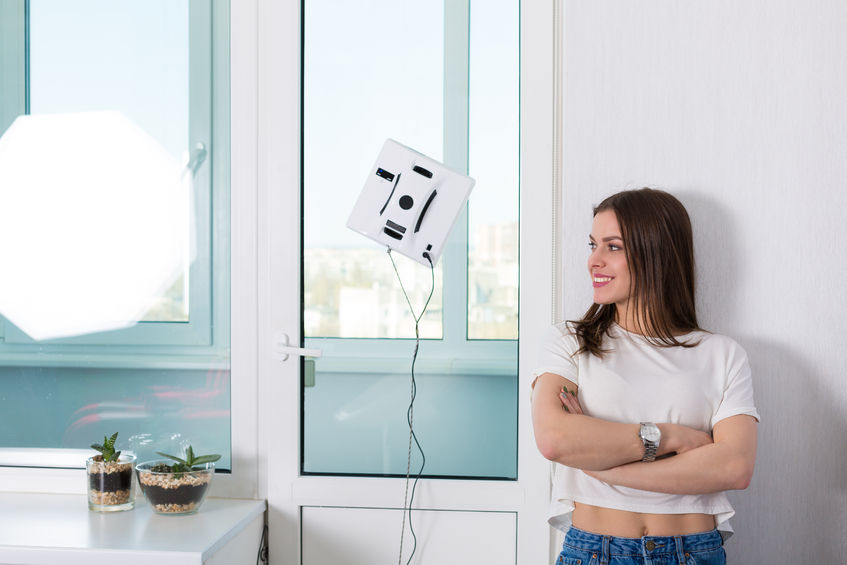 76498822 - woman cleaning windows at home with robotic cleaner