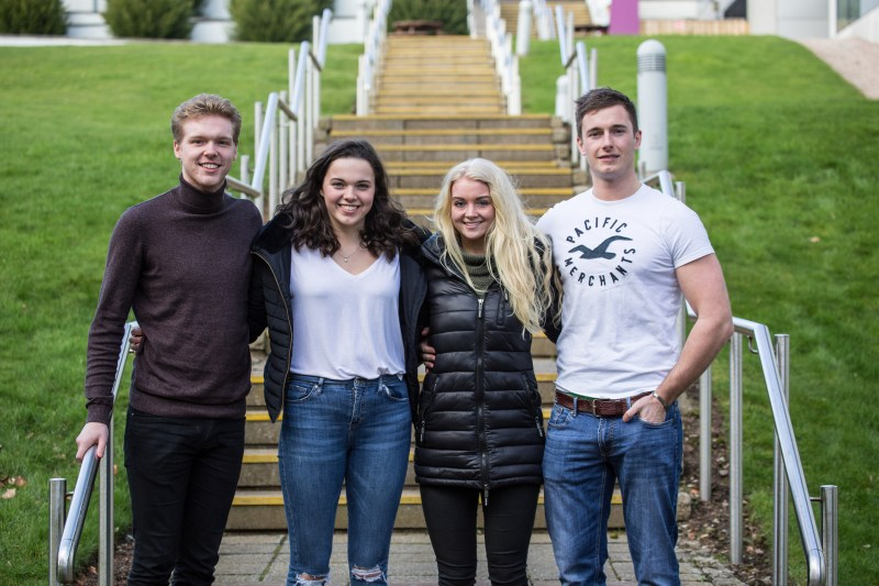 Four students standing in front of Aberdeen Business School.