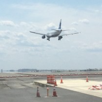Jet flies over part of Runway 4Left-22Right construction work during early phase of project to increase safety zones.