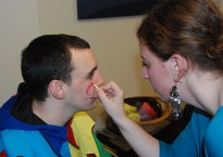 Sydney Bissonette applies make-up to the face of apprentice fool, Alec Donegan.