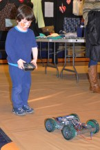 Mrs. Palmer's son, Jack, tries out the remote control car built by robotics students. Veritas photo