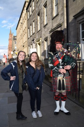Taylor Gallagher and Maddie Cedrone with a bagpiper in Scotland