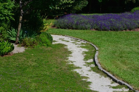 The edge of the home's thyme front lawn is bordered by a gravel path that leads to the side garden. To the right of the path is an immense grass lawn bordered by the driveway and a long garden bed.