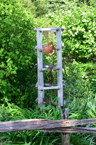 A wooden garden trellis is decorated with mask and pieces of metal.