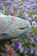 A blue ceramic fish in a bed of purple flowers