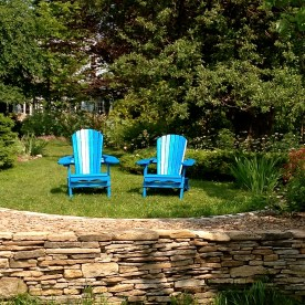 Two garden chairs are placed on a terraced lawn lined with a stone abutment.