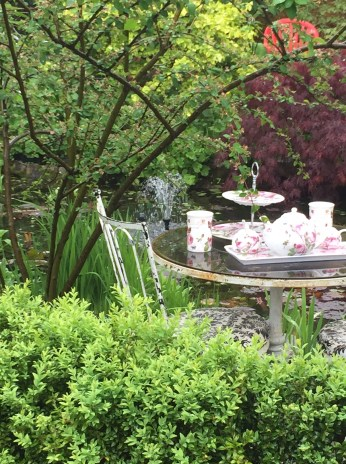 A back garden filled with plants features an all-weather tea table.