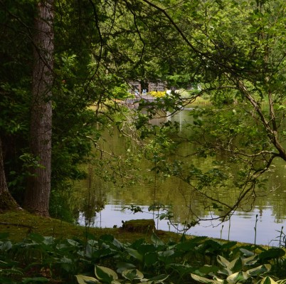 The swimming dock and pavilion is just seen across the pond surrounded by woodland.