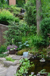 A waterfall, springing from the upper level of the home, flows down to a pond.