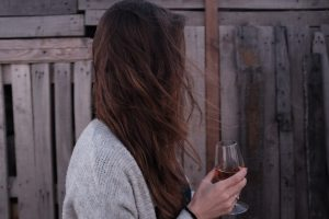 woman drinking wine by fence, signs of alcoholism