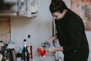 woman pouring drinks, signs of alcoholism