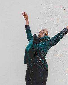 woman in green with confetti celebrating recovery