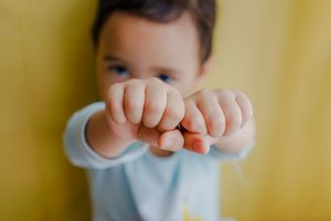 child with fists up secondhand drinking