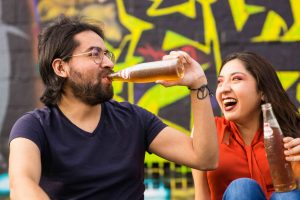 friends drinking and laughing how to stay sober when your spouse drinks