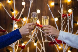 two women toasting glasses, coping with family drinking at holiday gatherings