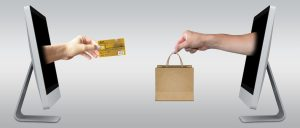 credit card and shopping bags exchanged by hands coming out of computer screens