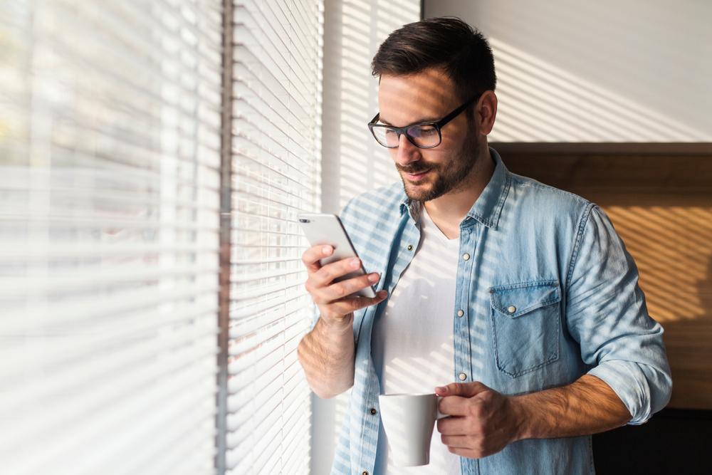 man standing by window using a telemedicine app