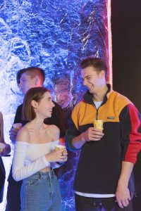teenage boy and girl holding drinks at a party