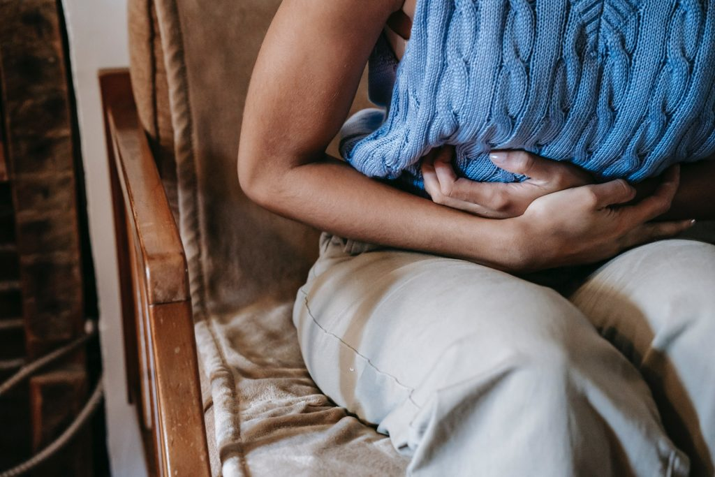 woman in blue sweater clutching stomach