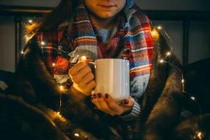 person holding hot mug wearing christmas lights