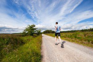 man running down road in the sunlight