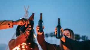 friends hoisting beer bottles over a campfire